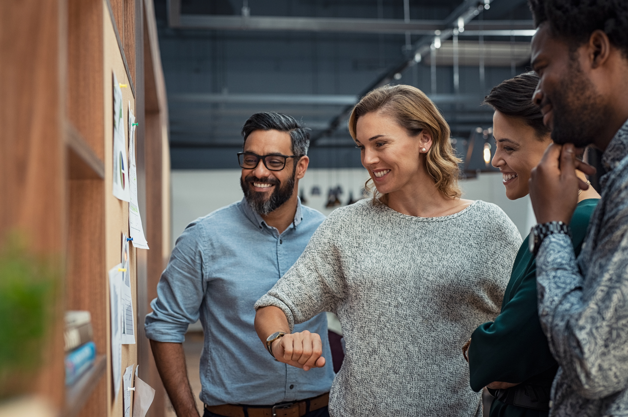 Group of mature businesspeople planning business strategy while looking at infographic displayed on wall. Business men and casual women looking at pie charts. Successful startup partners feeling happy on seeing progress in charts.